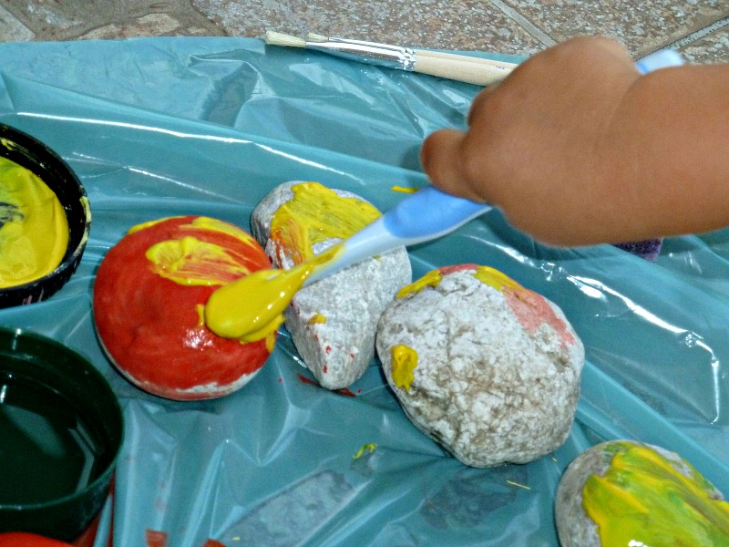 kids hand performing rock painting crafts