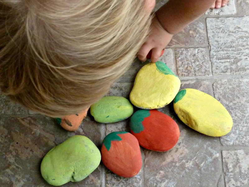 a person bent over a group of painted rocks for garden markers