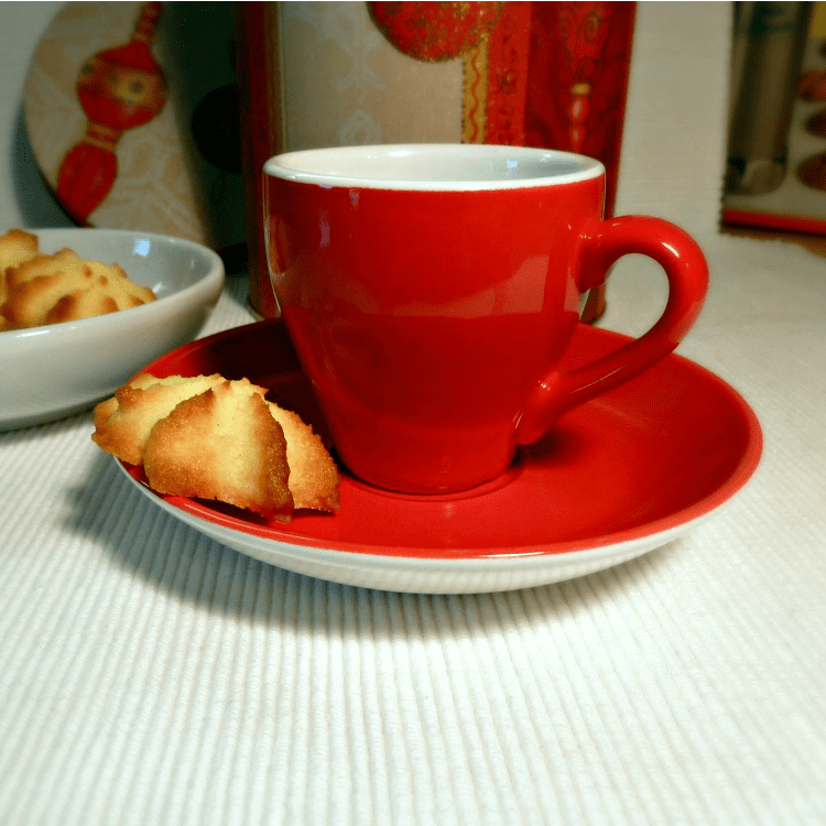 red coffee cup with a coconut cookie on a plate
