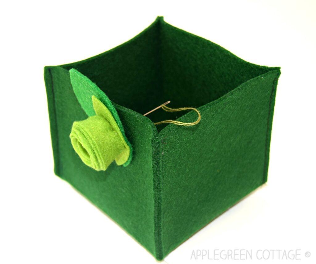 sewing a felt flower on the finished diy felt box