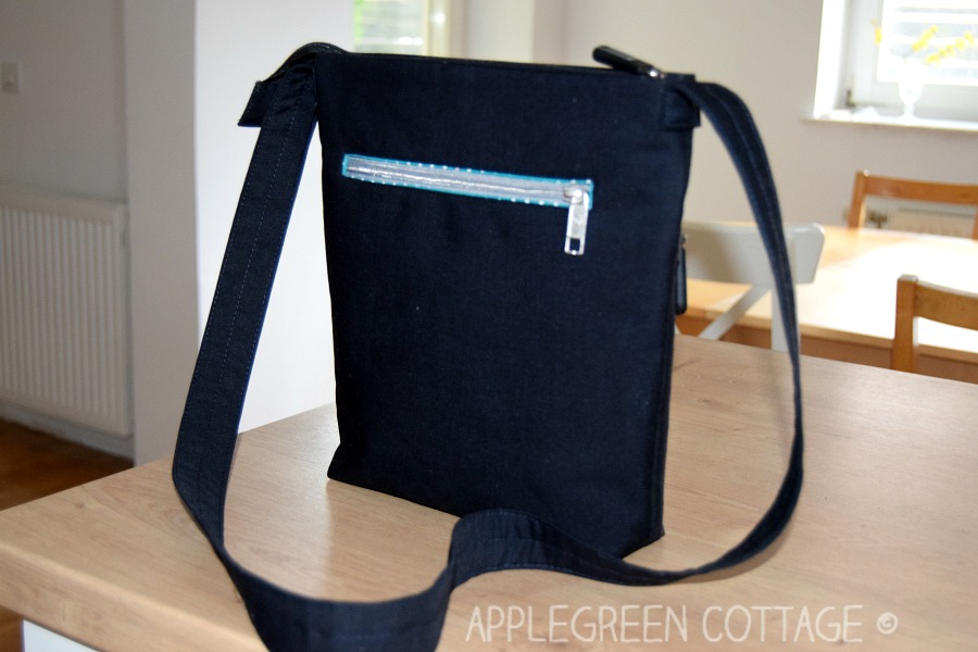 black diy crossbody bag on a wooden table in a house