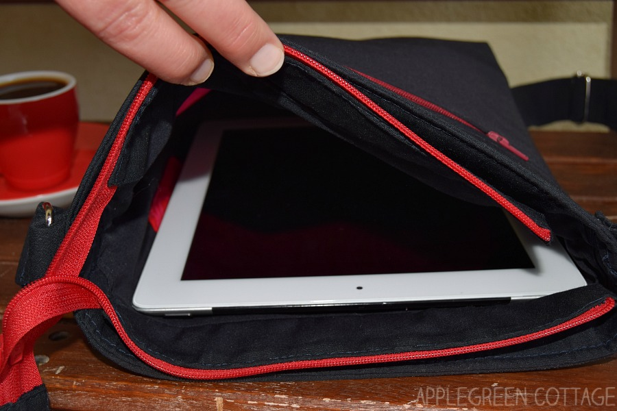 hand holding an ipad bag open with ipad visible in the bag