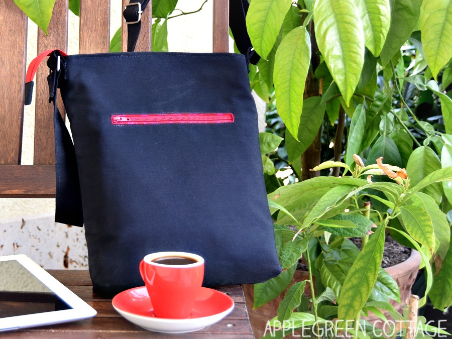 black diy ipad bag on a bench with greenery as backdrop and a red cup with cappucino