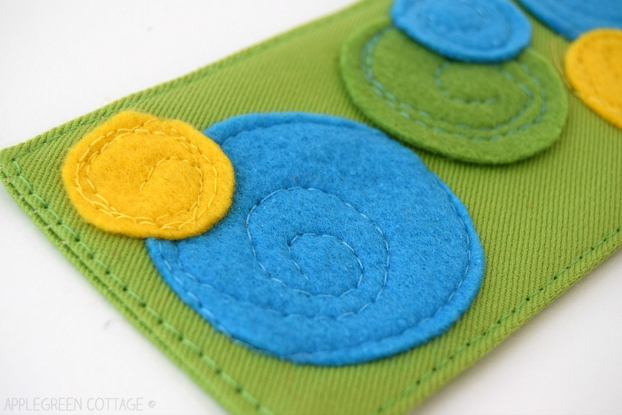 blue and yellow felt circles appliqued on fabric with a sewing machine