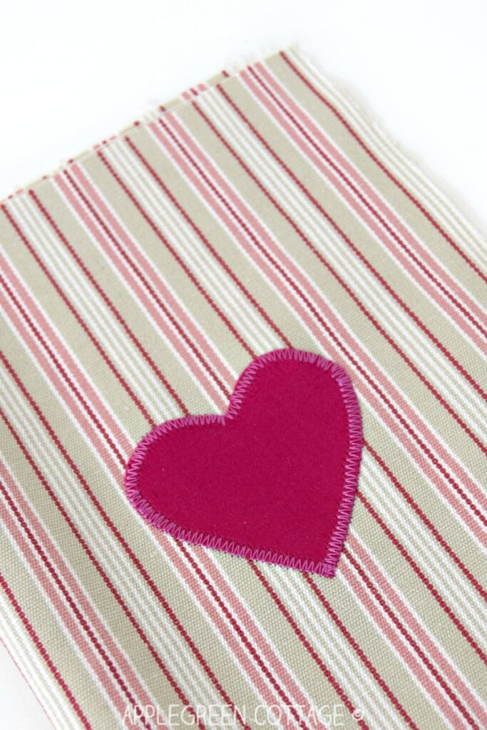 pink fabric heart applique sewn onto striped background fabric