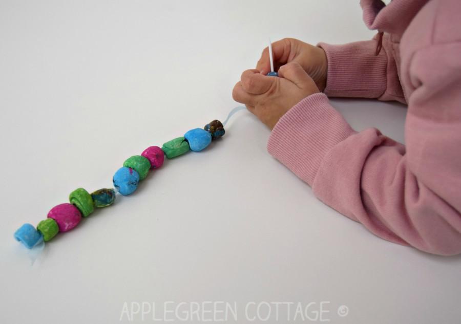 a kid threading diy clay beads into a diy bracelet