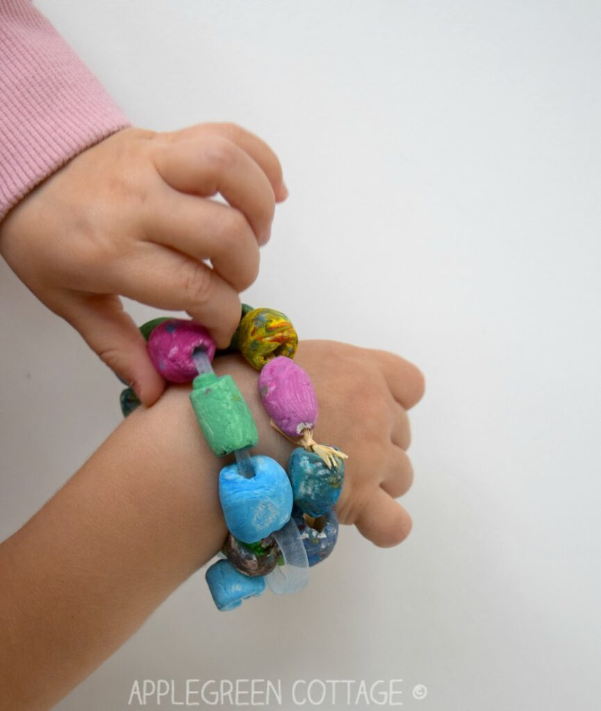 two painted diy bracelets made with air dry clay on a kids wrist