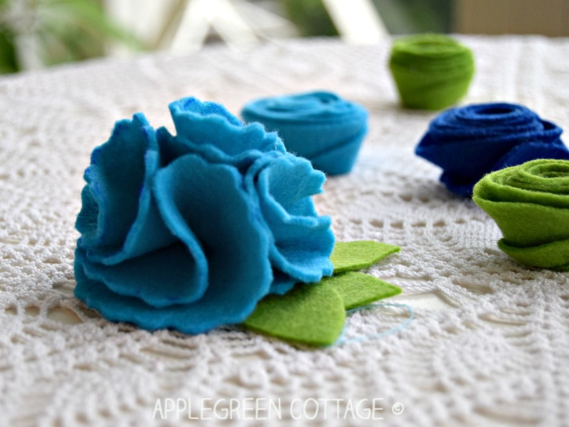 diy felt spring flowers with green leaves on a white surface