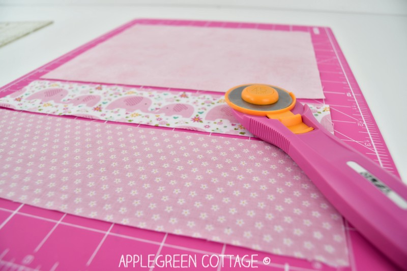 pink rotary cutter with fabric on cutting table