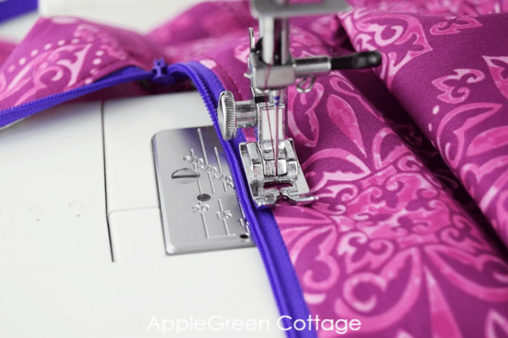 sewing zipper on a sewing machine with violet No 3 zipper and fabric in fuchsia print