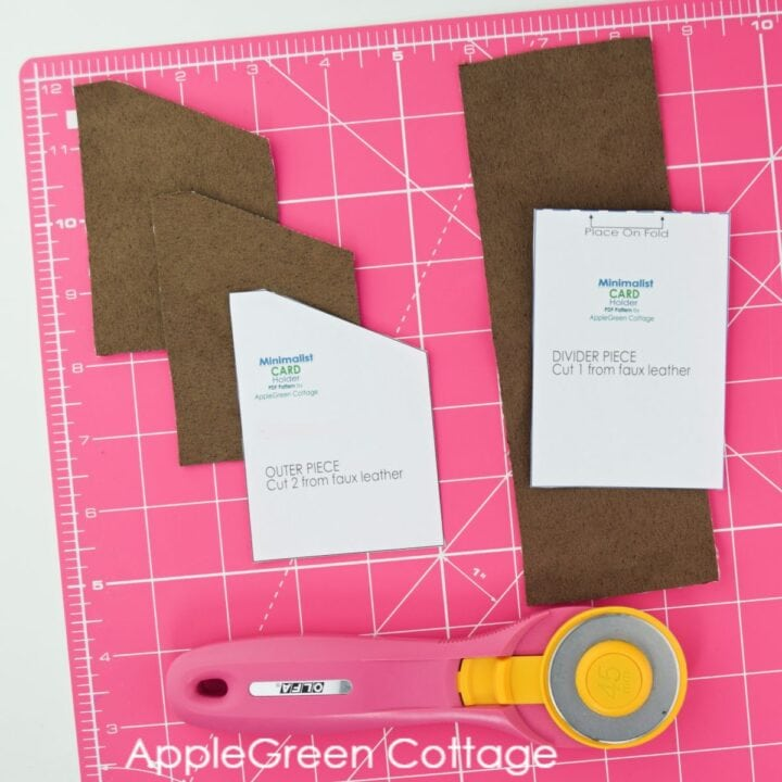 faux suede pieces cut for a front pocket wallet on a pink cutting mat